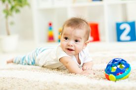 stock photo of crawl  - crawling funny baby boy on floor at home - JPG