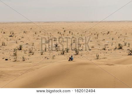 Man tourist in desert rub al khali in Oman sitting in sand view landscape