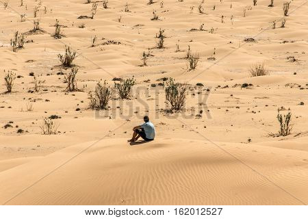 Man tourist in desert rub al khali in Oman sitting in sand view landscape 2