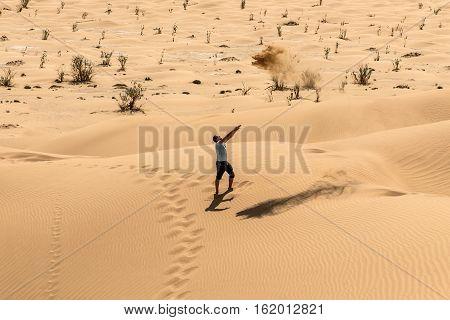 Man tourist in desert rub al khali in Oman throwing sand 3