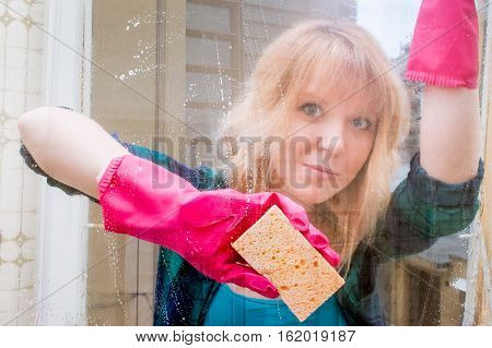 woman cleaning window with a yellow sponge and pink gloves. concept of hard domestic work and women doing  house work.