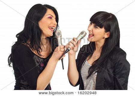 Two Women Singing To Microphones