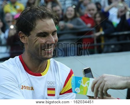 RIO DE JANEIRO, BRAZIL - AUGUST 12, 2016: Olympic champion Rafael Nadal of Spain gives autographs after men's singles semifinal of the Rio 2016 Olympic Games at the Olympic Tennis Centre