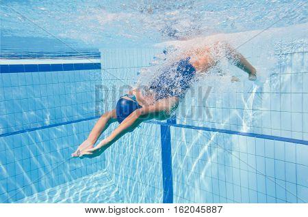 Female aquatic athlete starts backstroke lap, toned image, horizontal image