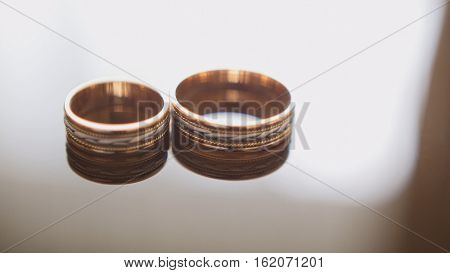 Golden wedding rings on mirror glasses table - one lies near another, close up