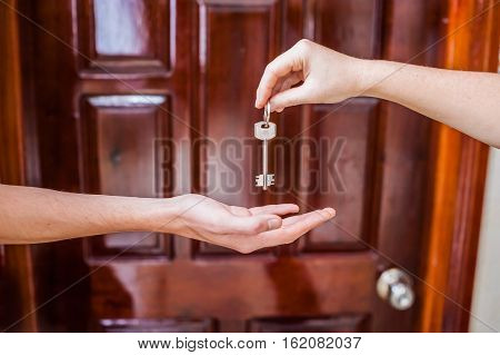 Female Hand Giving A Key To The House A Man's Hand On A Background Of A Wooden Door. Owning Real Est