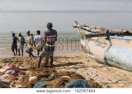 Galle, Sri Lanka - December 09, 2016 : Fishermen Stood And Work In The A Boat On The Beach At Galle