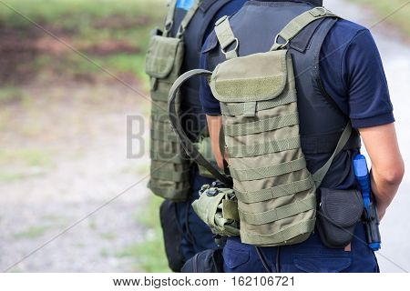 law enforcement with tactical hydration pack and tactical equipment in field training course with copy space
