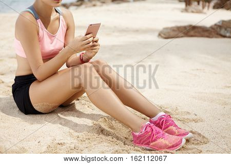Woman Athlete Messaging Her Friends Online Using Smart Phone While Relaxing On Beach After Running W