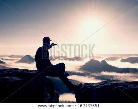 Silhouette Of Alone Hiker In Black And Cap Sit On Cliff. Blue Filter Photo. Man Looking To Mis