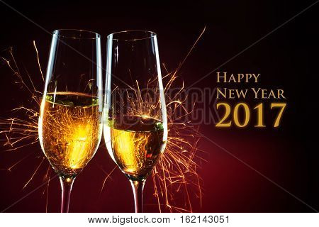 Party time with two champagne glasses and fireworks of sparklers against a dark red background with text Happy New Year 2017