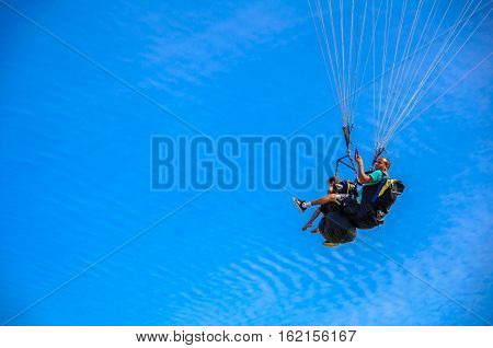 NITEROI, RIO DE JANEIRO, BRAZIL - FEBRUARY 23, 2016: Father and son flying on paraglider together in tandem on the background of blue sky