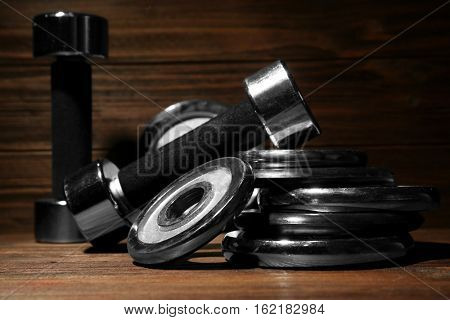 Dumbbells and weight plates on wooden background, closeup