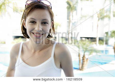 Portrait of a pretty brunette woman set against tropical poolside background.