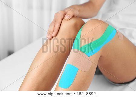 Female knee with physio tape, closeup