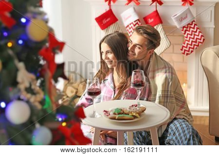 Young couple having Christmas dinner with wine and cookies in room