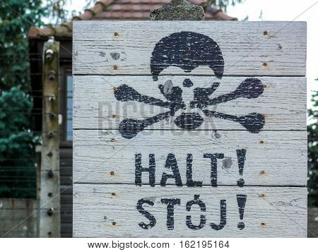 Stop sign in German and Polish with a skull and bones drawn in a prison establishment