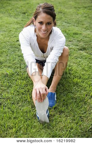 Female fitness trainer doing stretching for her calf and back of thigh muscle as part of warming down exercise.