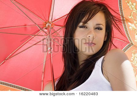 Portrait of a pretty young woman set against a vibrant colorful umbrella