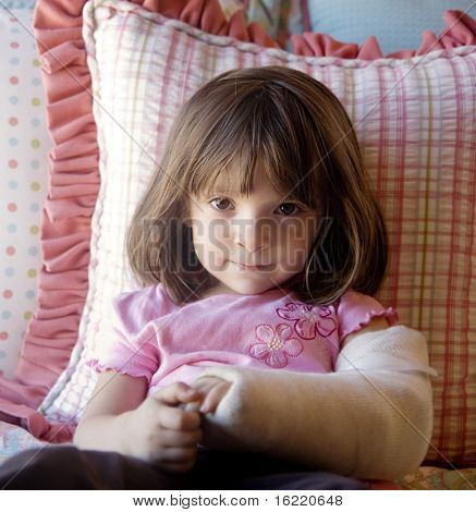 Young child laying in bed with fractured elbow and arm