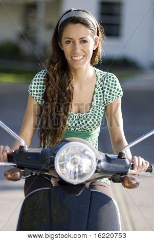 Junge Frau mit lange locken einen Roller fahren