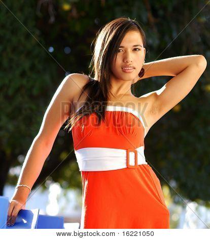 Attractive young multi racial woman swearing orange dress in fashion pose