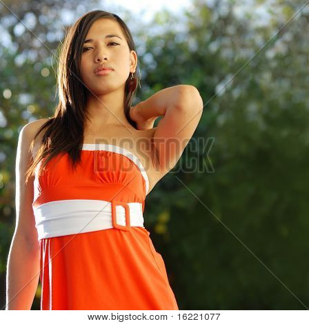 Attractive young woman swearing orange dress in fashion pose