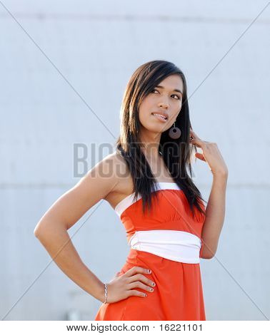 Attractive young woman swearing orange dress eyes looking up