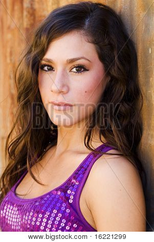 Beautiful sultry hispanic woman wearing purple sequin top.