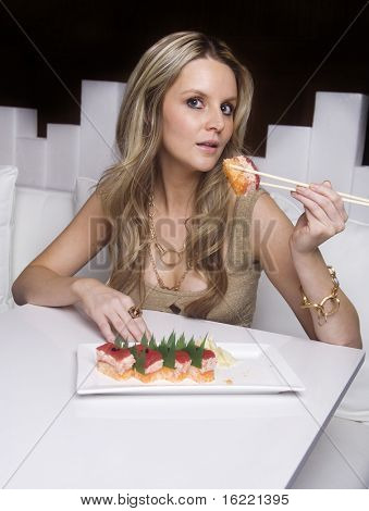 Beautiful sexy young woman eating raw sushi