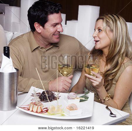 Casal jovem atraente, desfrutando de sobremesa em um restaurante