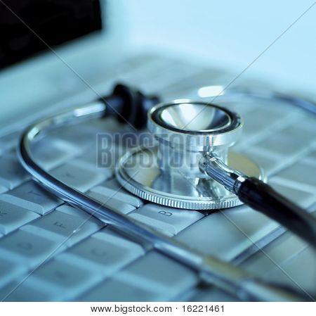 Tecnologia e medicina - prata estetoscópio sobre o teclado do laptop