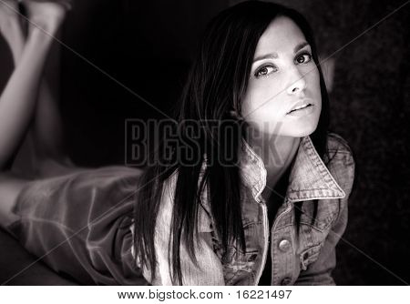 Beautiful young woman laying down with legs crossed eyes looking into the camera lens.  Shot in old vintage style.