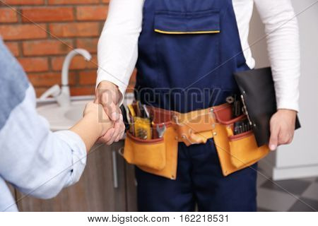 Plumber and woman shaking hands, closeup