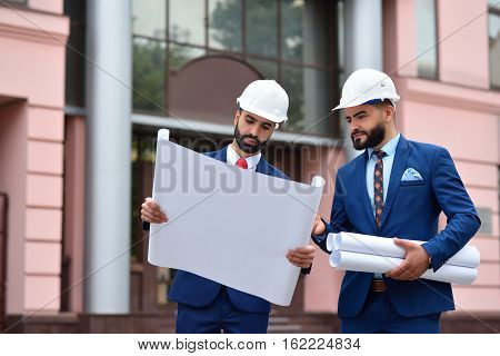 Two Arab Architects Looking At The Plan Outdoors