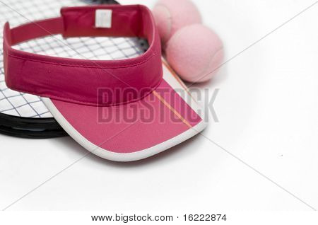 Tennis racket, pink sport visor and balls against white background