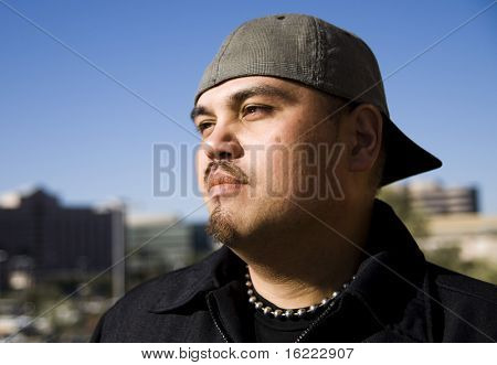 Portrait of a fashionable young man looking out at the city.