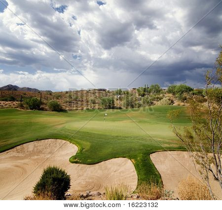 Dramatic sky with sunlight shining on beautiful desert golf course green in Scottsdale,AZ