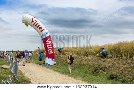QuievyFrance - July 07 2015: During Tour de France unidentified officials are installing a inflatable milestone on the cobblestone road in QuievyFrance on July 7 2015.
