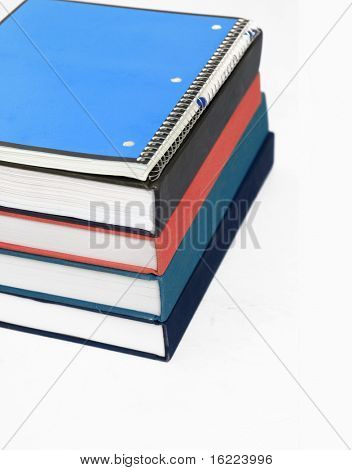 Collection or stack of text books with spiral bound note pad and pen sitting on top