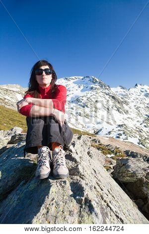 brunette sport woman red cardigan black trousers and sunglasses sitting relaxing and posing looking on rock blue sky and snow peak mountain in Gredos Avila Spain Europe