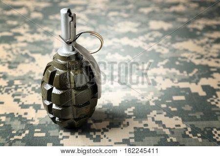Hand grenade on camouflage clothing