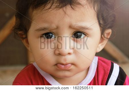 Closeup up portrait headshot suspicious cautious child boy looking at the camera. disbelief skepticism isolated grey wall background.