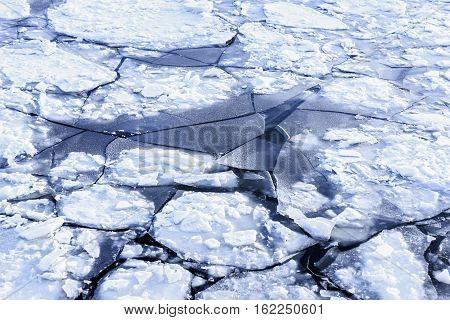 Big white ice in dark winter water