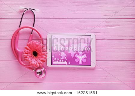 Stethoscope, tablet computer and flower on wooden background. Gynecology concept