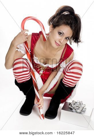 Sexy cute Christmas model wearing red velvet mini dress holding candy canes.
