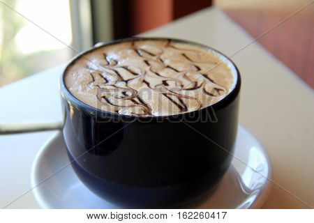 Tempting scene of large blue mug filled with hot,steaming latte, drizzled  with chocolate syrup.