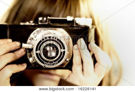 Small child holding vintage camera holding viewfinder to her eye