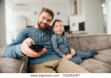 Photo of cheerful bearded father holding remote control while watching TV with his little cute son. Focus on remote control.