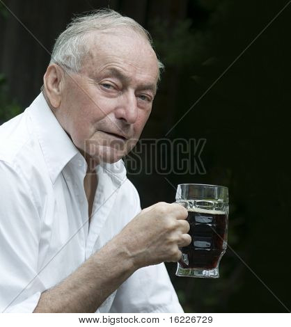 Senior man drinking a beer outside of pub.